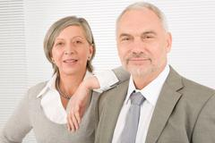 Senior businesspeople lean over shoulder colleague - stock photo