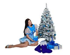 Attractive girl near Christmas tree and gifts - stock photo