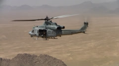 Stock Video Footage of closeup of us marine huey helicopter flying over desert of afghanistan (HD)