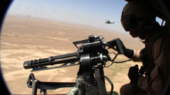 Helicopter door gunner looks for target over desert of middle east (HD) Stock Footage
