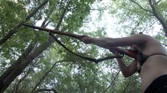 Woman in bikini firing rifle in woodland 4K Stock Footage