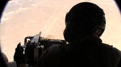 Stock Video Footage of silhouette of door gunner with afghanistan desert in background  (HD)