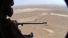 Helicopter door gunner looking over desert of afghanistan  (HD) Stock Footage