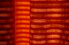 A vibrant orange curtain back-lit by the sun - natural photo texture perfect for - stock illustration