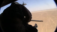 Helicopter door gunner sits back in fuselage after firing on enemy target (HD) Stock Footage