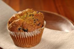 A warm, yummy, blueberry muffin on a wooden plate Stock Photos