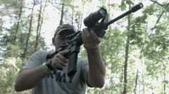Frontal view of man firing assault rifle in woods HD Stock Footage