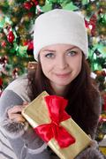 Woman in fur hat and mitten holding Christmas present Stock Photos