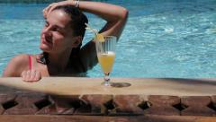 Woman swimming in pool and drinking Stock Footage