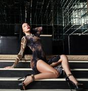 Sexy brunette woman sitting on stairs in nightclub Stock Photos