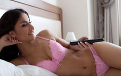 Young woman watching TV in bedroom Stock Photos