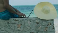 Man working on laptop on the beach Stock Footage
