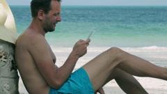 Man using cellphone on the beach, steadycam shot Stock Footage