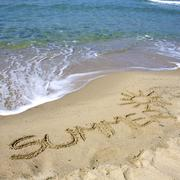 Stock Photo of summer written on sand with sun painted