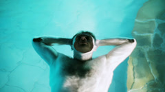 Man relaxing in the pool, steadycam shot Stock Footage