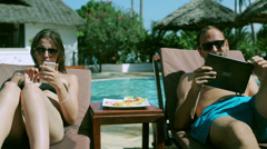 Couple using modern technology in the swimming pool Stock Footage