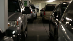 cars and people inside a busy parking garage steadicam - stock footage