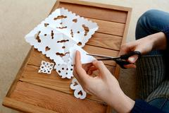 Stock Photo of Woman cutting paper into snowflake designs