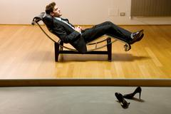 man lying on chaise longue - stock photo