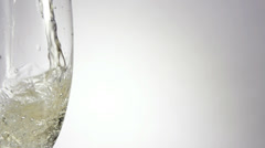 Stock Video Footage of Champagne pouring in glass with grey background, Slow motion