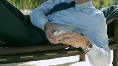 Businessman eating orange on sunbed, steadycam shot Stock Footage