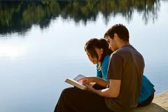 Couple reading the bible by a lake Stock Photos