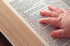 baby hand on open bible - stock photo