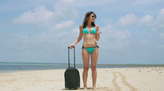 Woman with suitcase get lost on the beach Stock Footage