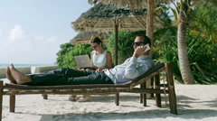 Businesspeople working on sunbed in exotic place Stock Footage