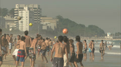 Young people enjoying themselves playing football on Ipanema beach, Rio, Brazil Stock Footage