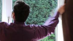 Guy closing the window curtains 2 Stock Footage