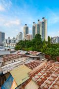 modern asian city discord with shacks and skyscrapers - stock photo