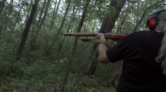 Over shoulder view of man firing high caliber rifle HD Stock Footage
