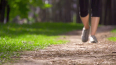 Runner feet running on a rural road closeup. Slow motion. Stock Footage