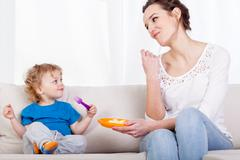 Mum and child eating meal together Stock Photos