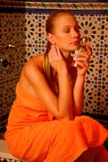 Woman with perfume in hand in the bathroom Stock Photos