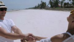 Couple spinning around on the beach, steadycam shot Stock Footage