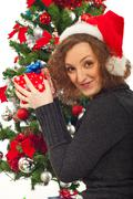Redhead woman with Christmas gifts near tree - stock photo