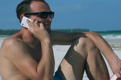 Man chatting on cellphone on the beach Stock Footage