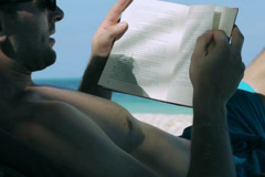 Man reading book on sunbed Stock Footage