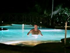 Man finish swimming in the pool at night Stock Footage