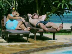 Couple talking and relaxing in the swimming pool, steadycam shot Stock Footage