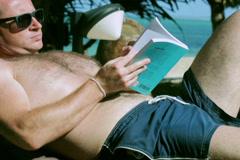 Man reading book on sunbed, steadycam shot Stock Footage