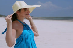 Happy woman standing on windy beach and holding hat, steadycam shot Stock Footage
