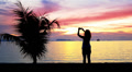 Silhouette of a Girl Photographs Beautiful Sunset. Thailand. Footage