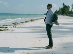 Businessman getting undressed on the beach Stock Footage