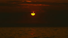 Amazing sunrise over the sea with bright sun disk and dark clouds. Stock Footage