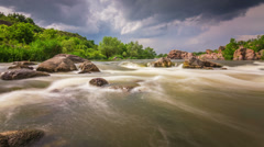 Timelapse of fast river stream flows through the stones with stormy clouds on Stock Footage