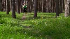 Young sports woman running on a rural road in the park. Sports lifestyle - stock footage