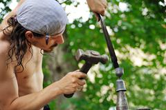 Young blacksmith hammering hot iron on anvil Stock Photos